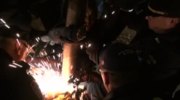 Sparks fly as NYPD officers cut a metal chain