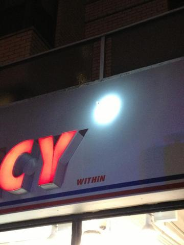 Flashlight shining on a bullet hole in Duane Reade on Third Ave