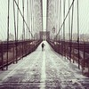 Not many people crossing the Brooklyn Bridge during a snowstorm
